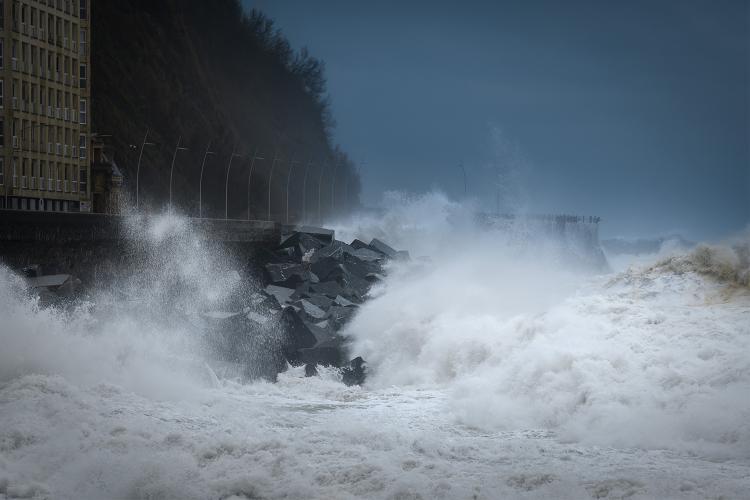 Una ola rompe en el paseo marítimo de San Sebastián.